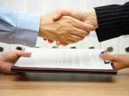 business partners are handshaking and exchanging contract after meeting